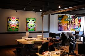 the office desk pool with two paintings and a large polytopia wall hanging