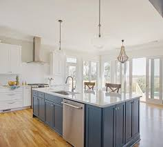 kichler pendants over a blue center island fitted with white quartz countertops and wood x back counter stools