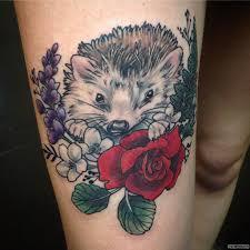 еж с розой и сиреневыми цветами тату на бедре у девушки добавлено