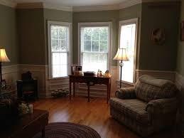 warm living room ideas: simple living room design with window bay gingham motive cushion armchair sofa light brown laminate