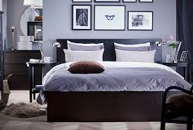 A black-brown HEMNES bed frame with a grey comforter and white striped  pillows.