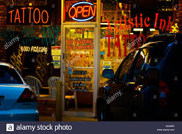 Neon Sign In Tattoo Parlor Window In Strip Mall Stock Photo