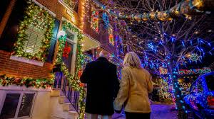 a couple admiring bright holiday lights at miracle on south 13th street in philadelphia