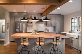 gray island with wooden countertop industrial bar stools 3 black pendant lights white tile backsplash french door refrigerator wood flooring ceramic sink
