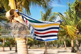 hanging beach towel. Beach Towel Hanging From Palm Tree, Blowing In Wind - Stock Photo
