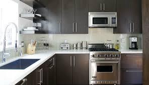 contemporary kitchen design with espresso kitchen cabinets white quartz countertops and stacked green glass tile backsplash