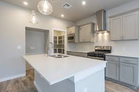 kitchen inside the alamosa timbercraft home with light gray cabinets white quartz counter top