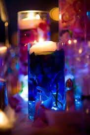 Glass cylinder wedding centerpieces with submerged flowers, floating candles  and LED submersible lights.