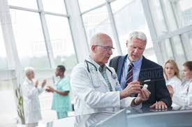 Pharmaceutical Representative Male Doctor And Pharmaceutical Representative Discussing Medication