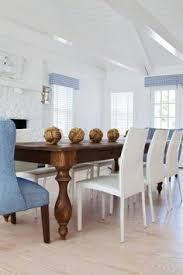 cote dining room features a dining table with carved wood legs lined with white leather dining chairs as well as blue dining chairs placed at each end of