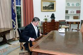 reagan oval office. c10216 president reagan looking in the oval office desk after inaugural parade 12081
