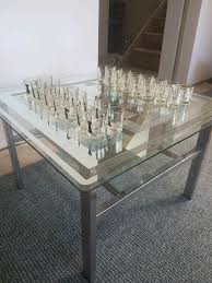 glass chess coffee table with shot glass playing pieces