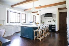 spacious transitional kitchen with blue island globe pendant lights between exposed beams and