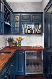 Small kitchens can handle deep blue cabinets when the walls are painted a  light neutral shade