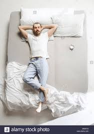 top view photo of young man sleeping in a big white bed top91 white