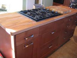 furniture brown wooden butchers block countertop connected by black stove on the floor simple