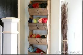 diy glove, scarf, hat, and shoe organizer mounted to a house's entryway wall