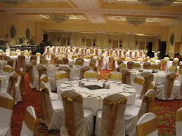 white chair covers and white tablecloths with gold sashes