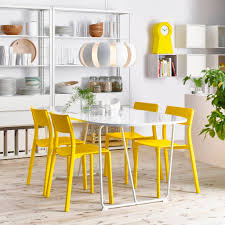 A dining room with an oval white dining table and yellow chairs. Shown  together with