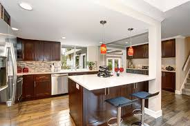 contemporary kitchen with brown cabinets glass backsplash and white quartz countertops