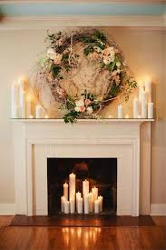Fireplace wedding ceremony with oversized wreath and pillar candles