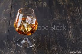 glass of whiskey with ice cubes served on wooden planks vintage countertop with highlight and