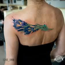 букет синих цветов в стиле акварель на спине фото татуировок