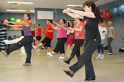 an instructor coaches a zumba cl in a fitness center
