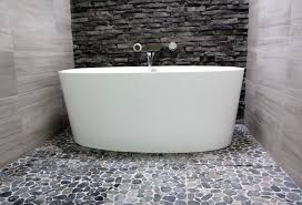 victoria albert ios bathtub in bathroom with pebble stone floor and drain