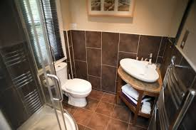 ensuite bathroom interior with brown tiles a corner hand basin and shower and toilet below
