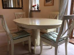 white round extending dining table and 4 chairs