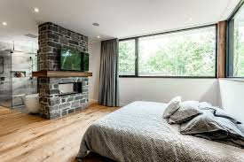 the bedroom features a large bed with a tv on brick wall below is the