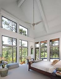 Upstairs, the bedroom's large glass windows and high ceiling create ...
