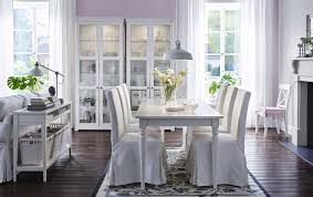 a large dining room with a white dining table and six chairs covered in white cotton
