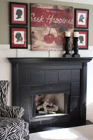 image of outstanding painting ceramic tile fireplace surround with large wood candle holders on black wood