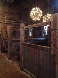 rustive horse barn with chandelier over open stalls