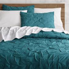 an infinite field of hand guided pintucks creates soft rippled texture on cotton duvet cover fastens with ons melyssa teal bed linens is a
