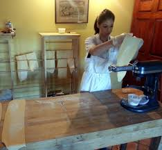 right next to the bar out in the dining room a long wooden farm table was set with a stand mixer and pasta roller