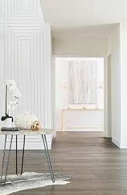 elegant contemporary foyer boasts a round gray wood top accent table placed on a small black and white cowhide rug in front of white walls accented with a