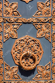 handle old black door with a golden pattern of metal forging close up of