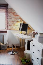 ... Home office nook in an attic with partial brick wall