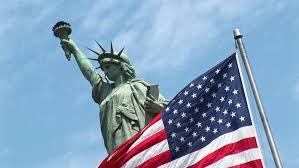 american flag waves in front of the statue of liberty circa 2006 in new york