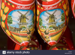 pair of clogs sabot or dutch wooden shoes painted with windmill and tulips with holland sign