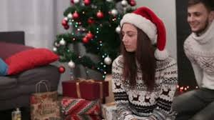 Young Attractive Man Closing Eyes Of Woman And Giving Here The Giving Gifts On Christmas