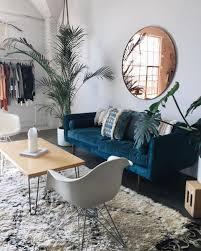 blue sofa living room design. blue sofa + beni eames chairs circular mirror clothing rail tall plant living room design c