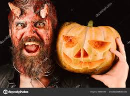 man wearing scary makeup holds pumpkin on black background demon with horns and scary smile face holds carved jack o lantern party concept