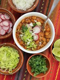 pozole rojo is a hearty clic mexican soup or stew traditionally made with pork broth pork hominy and es then topped with garnishes such as lime