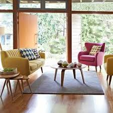 retro shapes are enhanced by plush upholstery in hot pink and sunshine yellow to create a seating area full of