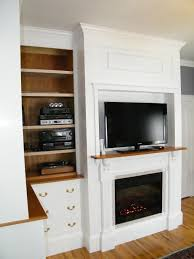 interior black fireplace with television above beside brown wooden shelves and white drawers placed on