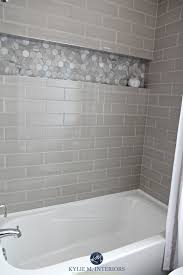 bathroom with bathtub and gray subway tile shower surround with niche or alcove in hexagon marble tile greige accent tile kylie m interiors design